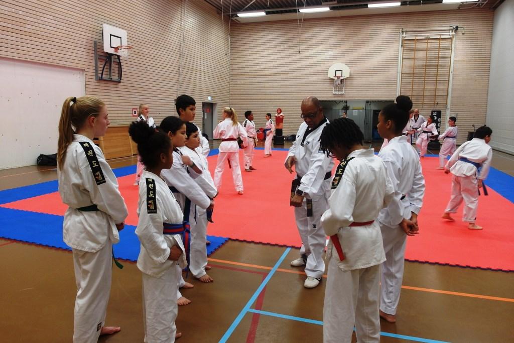 Sylvestro van der Kooye geeft instructies aan de leerlingen Foto: Dennis Lee Kong © Persgroep