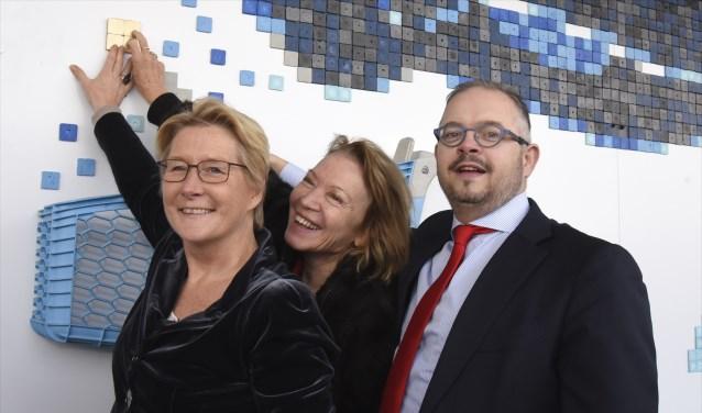 Anneke de Vries, Winnie Sorgdrager en wethouder Rogier Tetteroo plaatsen het  gouden tegeltje in het kunstwerk aan de gevel van de AH-supermartk. Foto: Marianka Peters