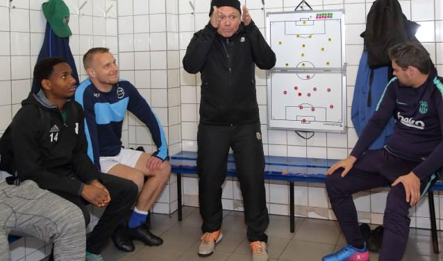 Trainer John Retel Helmrich geeft voor de wedstrijd in gebarentaal met gesproken tekst en op een groot bord uitleg over de opstelling en tactiek. Links, met blauwe sweater, speler Patrick Lanser. (Foto's: Rob Kamminga)