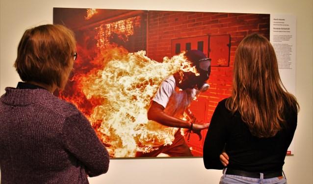 Twee bezoeksters bekijken de winnende foto van de World Press Photo, die te zien is in de Willem Twee in Den Bosch. Op de foto staat een brandende man tijdens een protest in Venezuela.
