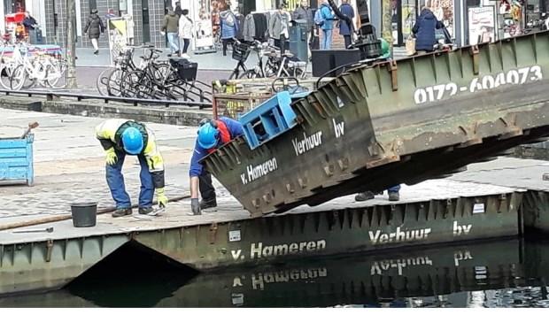 Werklui druk bezig de pontons aan elkaar te verbinden. (foto: Aad van Zon)