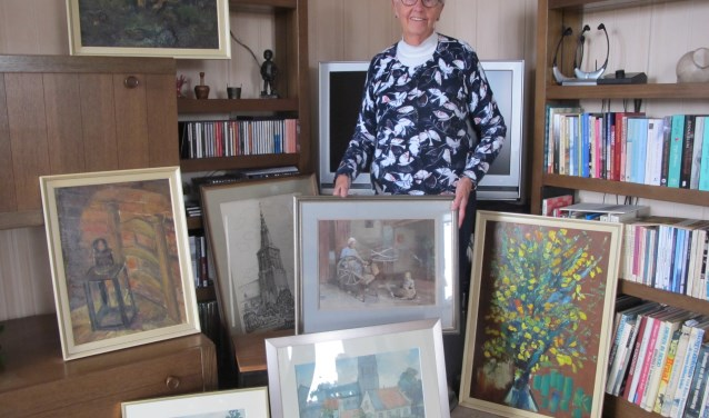 Mevrouw Naessens-van Zogchel in haar huis in Ede te midden van de zeven geschonken schilderijen. Foto: Willem van Vossen.