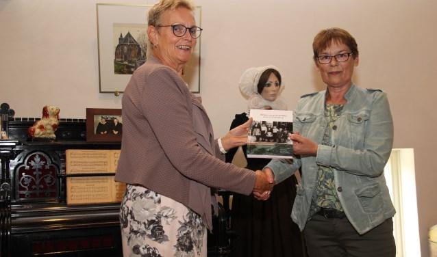 Wethouder Liesbeth Vos nam het eerste exemplaar van 'Hinne en weerumme, deur 't Winkeldarp' in ontvangst. Foto: Alida Bosma