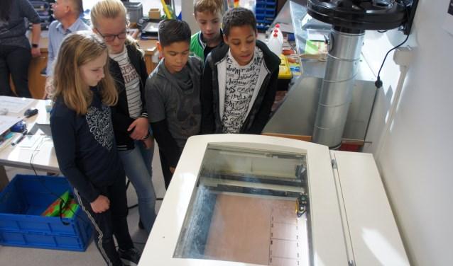 Leerlingen van het Kompas kijken hoe de lasersnijder de onderdelen voor een vogelhuisje uitsnijdt. (Foto: Thea van der Raaf)