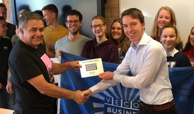 Economiedocent Jasper Verhoef krijgt de plaquette uitgereikt van Theo de Roos (voorzitter van de Vecon). FOTO: Kalsbeek College
