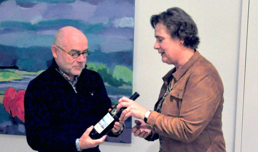 Henk Hulshof neemt de eerste fles met zijn etiket in ontvangst, op de achtergrond het schilderij
