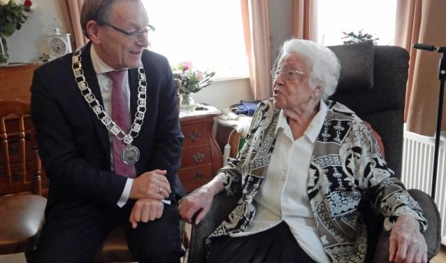 Mevrouw Brinkman maakt met zichtbaar plezier grapjes met burgemeester Koos Janssen tijdens haar honderste verjaardag.