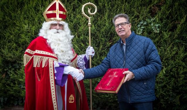 Frank Tengnagel (rechts) draagt het grote boek van Sinterklaas over aan Mark van Zuiden. (Foto Berco Buter)