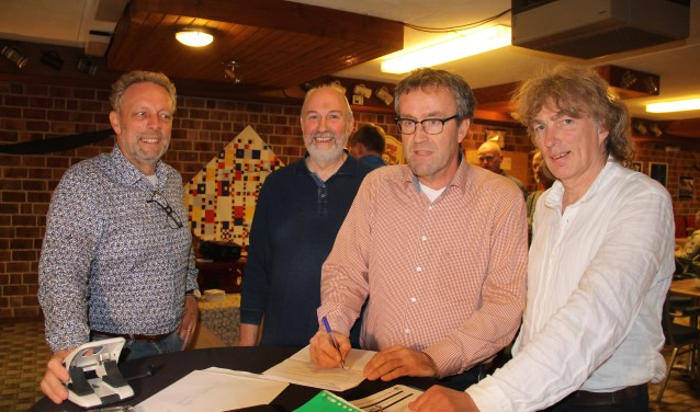 Stef Tiggeloven tekent het contract. Joop ten Dolle (links), Benny Reesink (voorzitter) en Willem te Voortwis (secretaris/penningmeester) kijken toe.