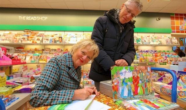 Netty Gebbing signeert het boek dat Martin Joosten uit Zaandam heeft gekocht. (foto: Kirsten den Boef)