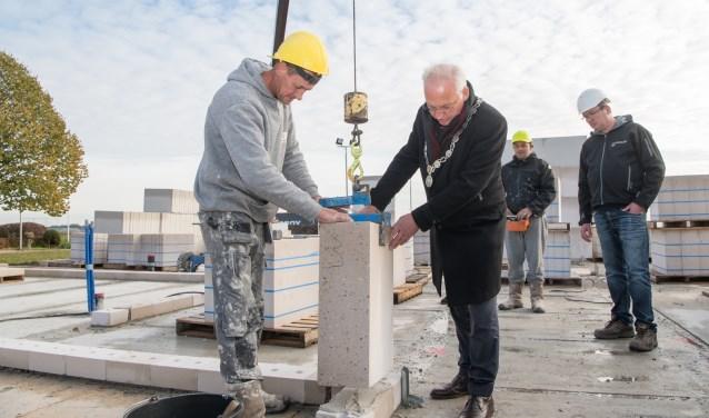 Met uiterste precisie plaatst burgemeester Dirk van der Borg de eerste steen. (Foto: Alex Willemsen)