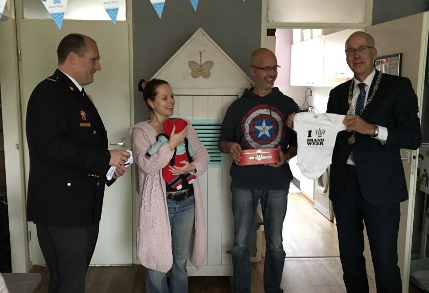 Burgemeester Arend van Hout (rechts) en Jeroen Beskers van de brandweer (links) overhandigen Ramona Reessink en Maarten Braun brandpreventieproducten. Baby Ziggy-Joe krijgt er weinig van mee.