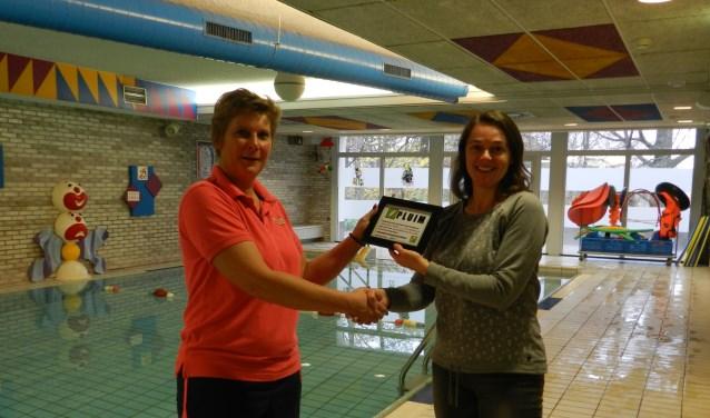 Francis van Mullem van zwemschool Okidoki neemt de PLUIM in ontvangst van Rianne Jansen voorzitter van Stichting Op Eigen Tenen.