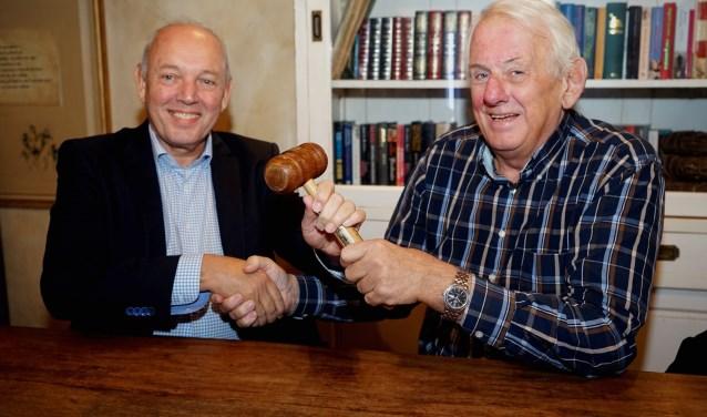 Voorzitter Willem Stok geeft de voorzittershamer over aan Jozèf Rutten. (foto: Tom Oosthout)