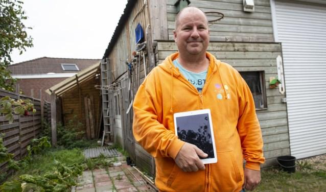 Nico Plönes staat met de tablet van Luuc voor de loods, die plaats maakt voor het nieuwe zwembad. (foto: Jimmy Israël)