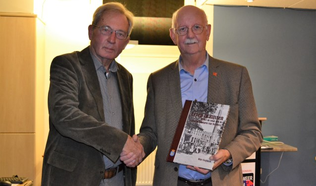 Wim Vlogtman (links) heeft zojuist het eerste exemplaar van zijn boek overhandigd aan voorzitter Jan Bakker van het Rijssens Museum. Foto: Jan Joost.