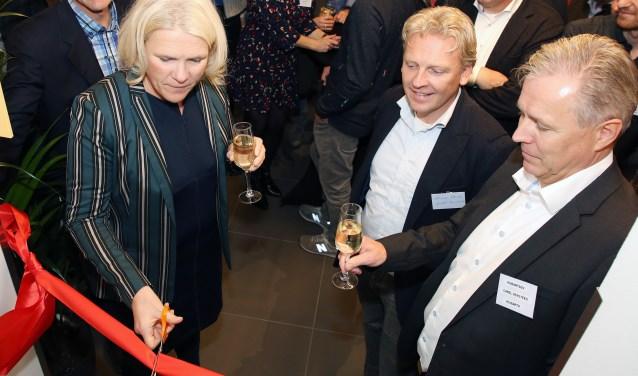 Wethouder Lianne Smit Volkers knipt het lint door, onder toeziend oog van Harmen Alberda (m) en Carel Versteeg (r). Foto: Theo van Sambeek.