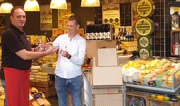 Een trotse Sjaak Vennink overhandigt zijn eerste flesjes aan de eigenaar van de Vershoek. (foto: pr)