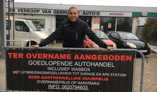 Lizette van de Velde bij het bord voor haar autozaak aan de Kuijerdamseweg in Ellemeet. FOTO: Gerrit van Loon