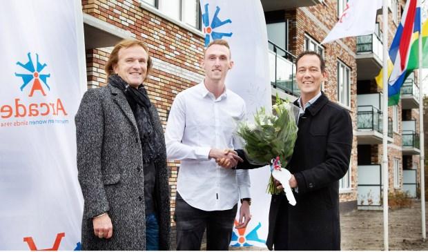 Wethouder Boudewijn Revis (stadsontwikkeling en wonen) en René Lemson, directeur-bestuurder bij Arcade, reiken de eerste sleutel uit aan Melvin Hardon.