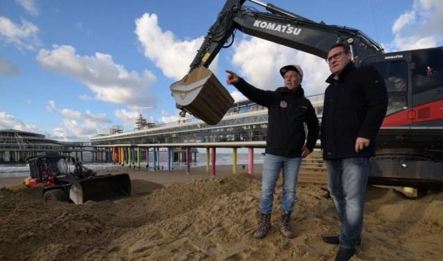 Wethouder Richard de Mos en ontwerper van de baan Greg Atkins. Samen gingen ze vrijdag aan de slag om de eerste obstakels op het strand op te werpen.