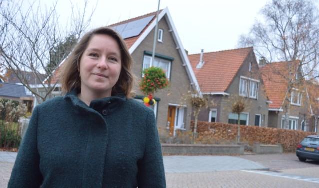 Marianne Kooman met op de achtergrond haar nieuwe woning in Wolphaartsdijk. FOTO: Timo van de Kasteele