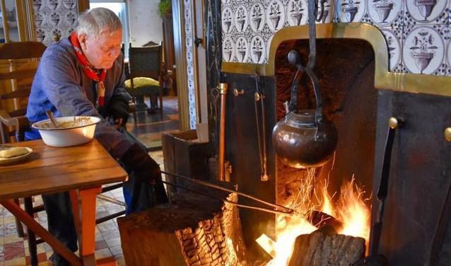 Het wafelijzer, met daaraan een lange tang, werd boven het open vuur gehouden, totdat het beslag gaar was.