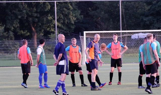 De spelersgroep van RKDVC luistert naar de aanwijzingen van trainer John Meijs. Foto: Wout Pluijmert