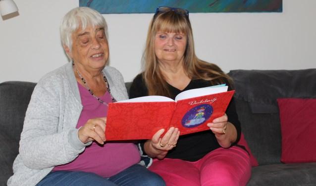 Trees en Isabelle bekijken het boekje Duikelaartje. FOTO: Lydia van der Meer