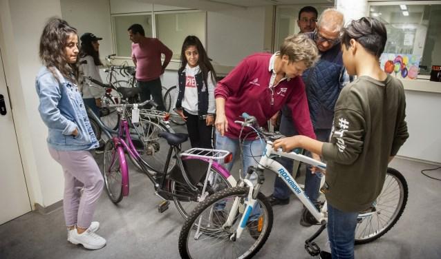 De familie Hoessein zoekt fietsen uit. Jolanda Smits - van Son (met rode trui) en Willem van Engelen (met blauwe bodywarmer) van Wij gaan fietsen geven advies.