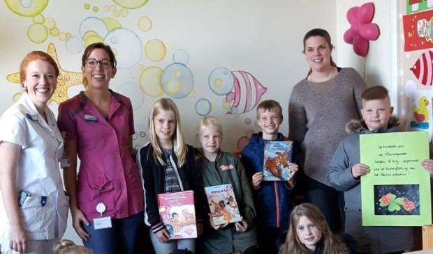 Leerlingen van KBS Mariëngaarde overhandigen een cheque en kinderboeken aan de kinderafdeling van het Beatrixziekenhuis. Eigen foto