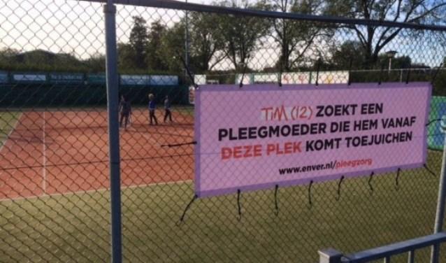 Pleegzorg spandoek voorbeeld bij Tennisvereniging Smitshoek in Barendrecht. Opschrift op spandoek is: Tim (12) zoekt een pleegmoeder die hem vanaf deze plek komt toejuichen.