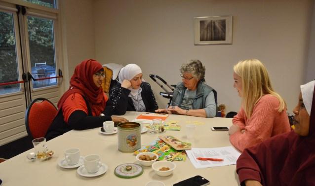 v.l.n.r.: Amal, Walaa en twee vrijwilligers. Samen zijn ze Nederlandse gezegdes aan het oefenen. Foto: Jan Piels