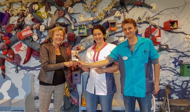 Mirjam Hagen krijgt het zakboekje overhandigd door Elizabeth Straalen en Paul Kraan