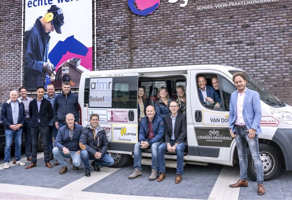 Sponsors en medewerkers van Symbion verzamelen zich in en rond de schoolbus van de Liemerse praktijkschool.