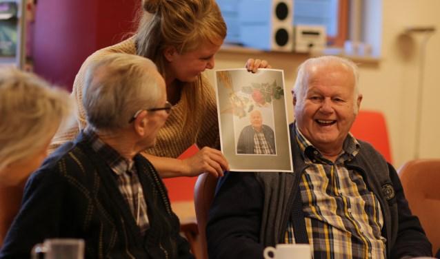 """Heike laat de heer Hermans het resultaat zien van zijn zelfportret voor Portret Boeket. """"Hoe zat het met die roos?"""" (foto: Feikje Breimer)"""