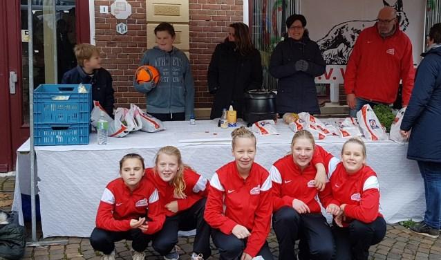 Vrijwilligers en jeugdleden tijdens de verkoop van rookworsten op de markt.