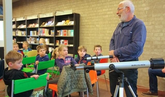 Deskundige Ewald Nijenhuis laat de kinderen in de bibliotheek in Bemmel zien hoe een sterrenkijker werkt. (foto: Kirsten den Boef)