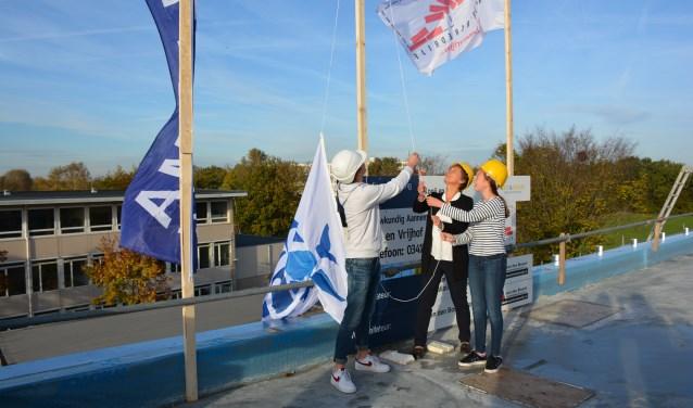 Het hijsen van de vlag op het dak van de nieuwe aanbouw. Foto: Hanna de Groot