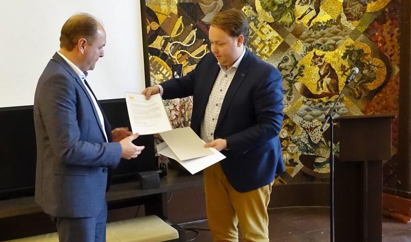 Wethouder Jeroen Diepemaat overhandigtde prijs aan Peter Winterman, bestuurder van de woningbouwcorporatie Ons Huis In Enschede.