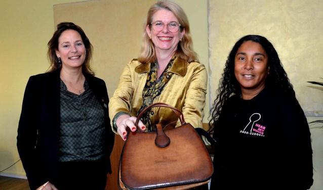 Burgemeester nog met tas, rechts Marlene van de Veer, links Marion Bootsma. Zondag is die tas te koop in het Nutshuis.