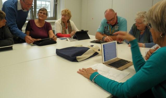 In het Tablet Café op het educatieplein (hoofdbibliotheek) werken ouderen gezelig samen op hun tablet. Foto Kees van Rongen