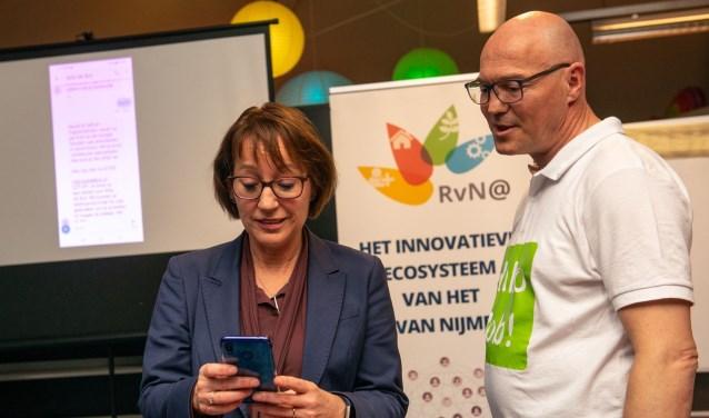 Ronny Hendrikx, ontwikkelaar van Bob de Bot, helpt gedeputeerde Bea Schouten om de eerste boodschap te sturen.