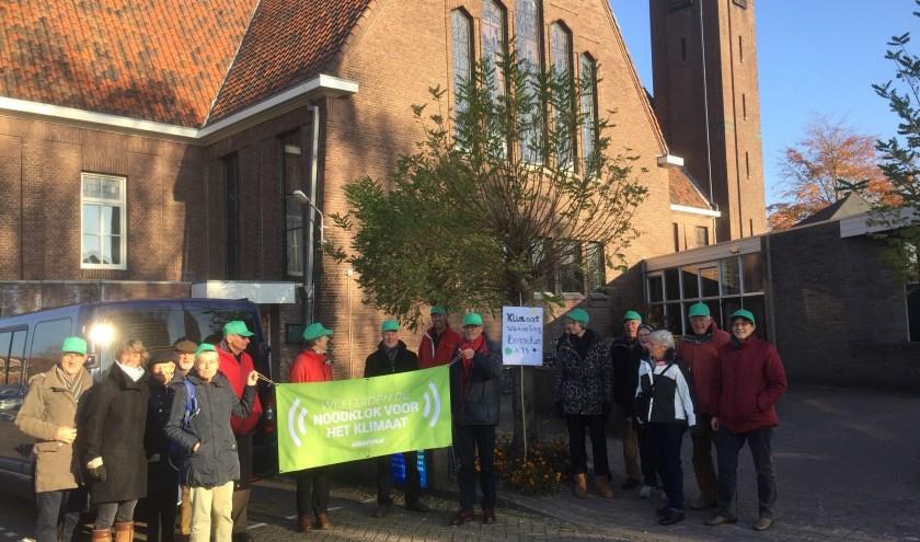 Voor de Brinkstraatkerk staan deelnemers die de vlag met de tekst: 'wij luiden de noodklok voor het klimaat' dragen
