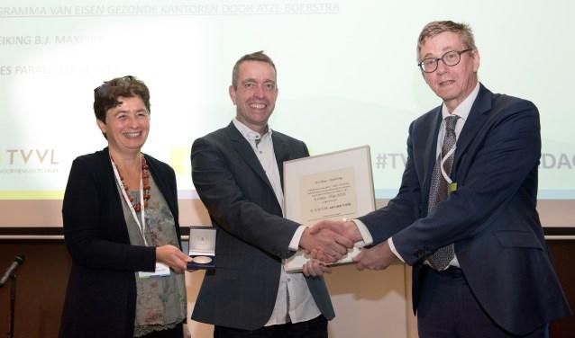 Alet van den Brink (midden) krijgt de medaille en oorkonde uit handen van juryleden Laure Itard en Wim Zeiler.