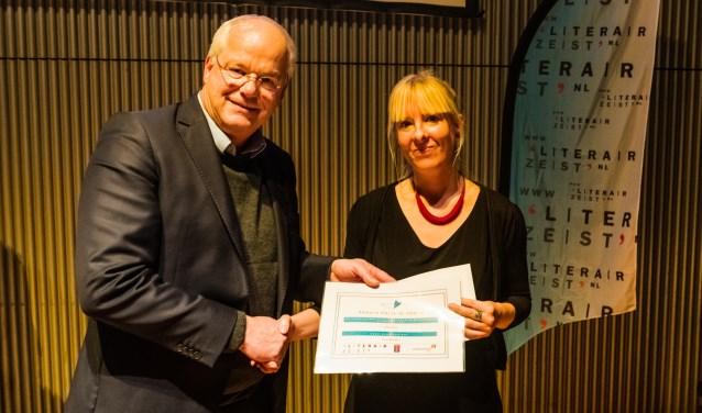 Jan Arns ontvangt de LiteratuurPrijs Zeist uit handen van wethouder Mel Boas op 23 november in De Klinker in Zeist