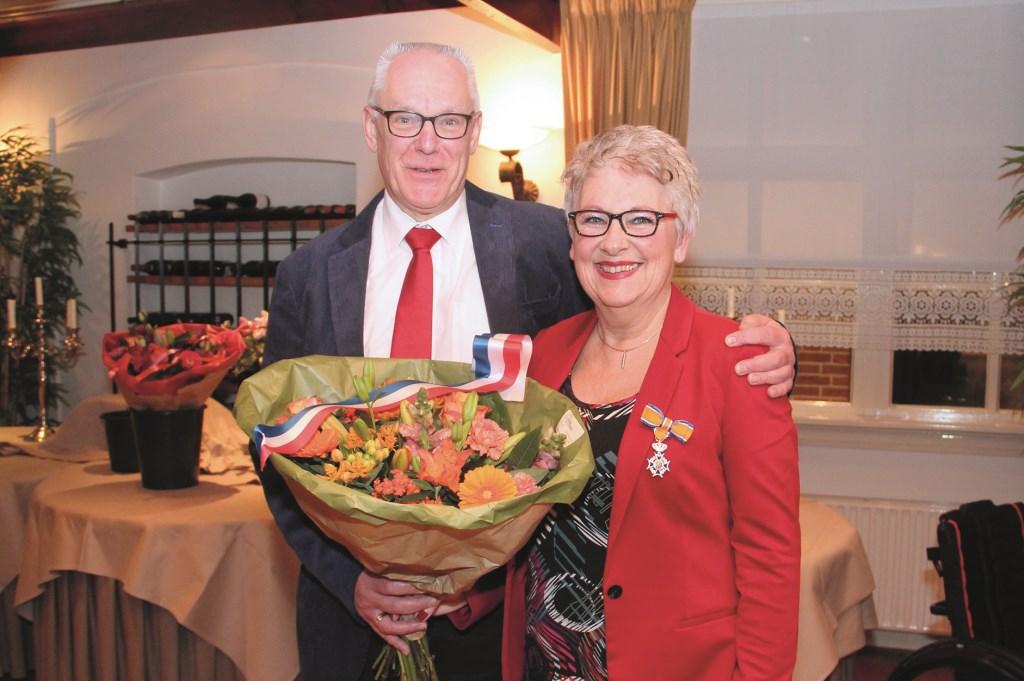 Gonda Pranger-Goudzwaard met koninklijk lintje, bloemen en haar man Rien.
