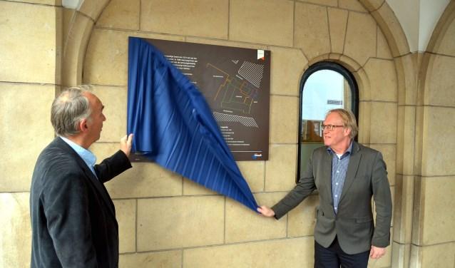 Voorzitter van de Historische Vereniging Vlaardingen Ted Hartman (links) en wethouder Bart de Leede onthullen het vernieuwde ANWB-bord aan de muur van het stadhuis te onthullen (Foto Frans Assenberg).