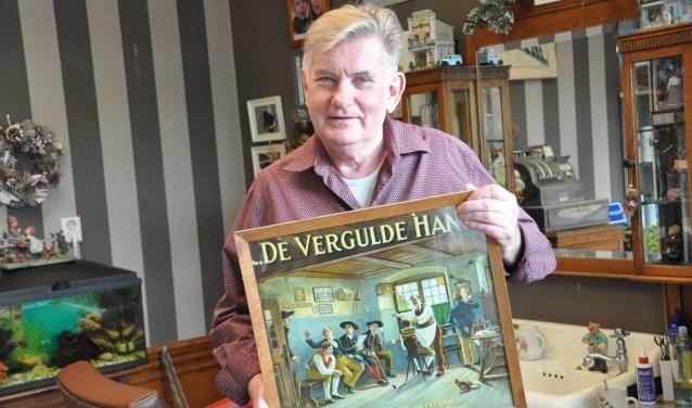 Kapper Hans met de prent die bij zijn vader in de zaak hing. 'Zo wilde ik het ook'. FOTO: Julie Houben