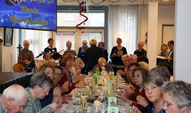 De gasten en hun vrijwilligers genieten van het voorgerecht met  zangkoor 't Zingt op de achtergrond. Foto: Theo van Sambeek.